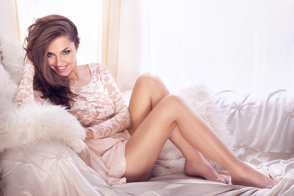 Young beautiful smiling woman relaxing on white couch.
