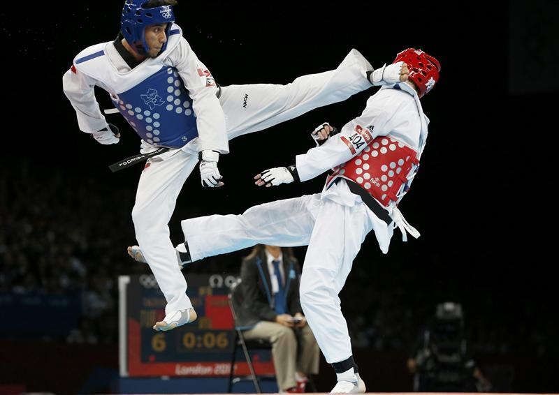 Turkey's Servet Tazegul (L) kicks Britain's Martin Stamper during their men's -68kg semifinal taekwondo match at the ExCel venue during the London Olympic Games, August 9, 2012. REUTERS/Kim Kyung-Hoon